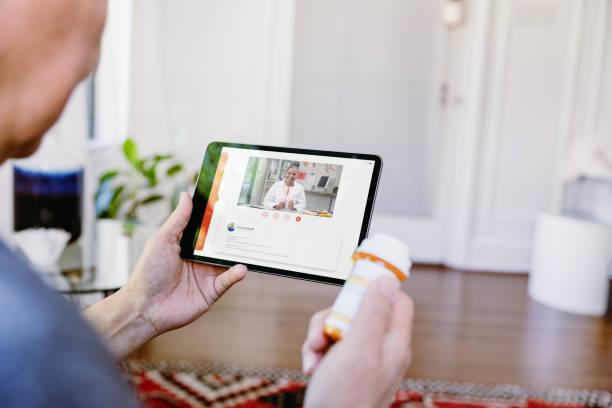 unreconocible senior hombre video chats con el médico - telehealth fotografías e imágenes de stock