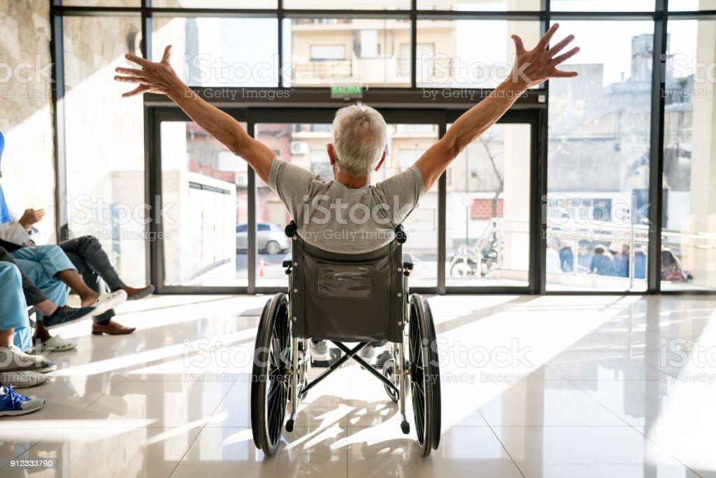 Méconnaissable patient supérieur quittant la clinique sur une chaise roulante avec ses bras vers le haut - Photo