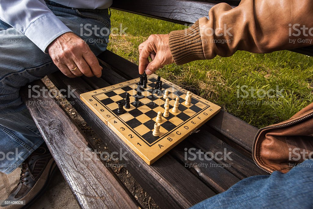 Unrecognizable senior people playing chess on a bench outdoors. stock photo