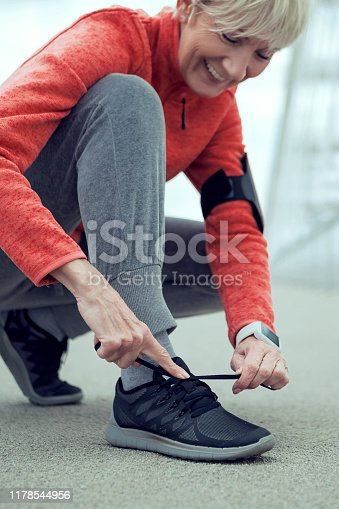 Unrecognizable senior person tying shoelaces on sports sneakers