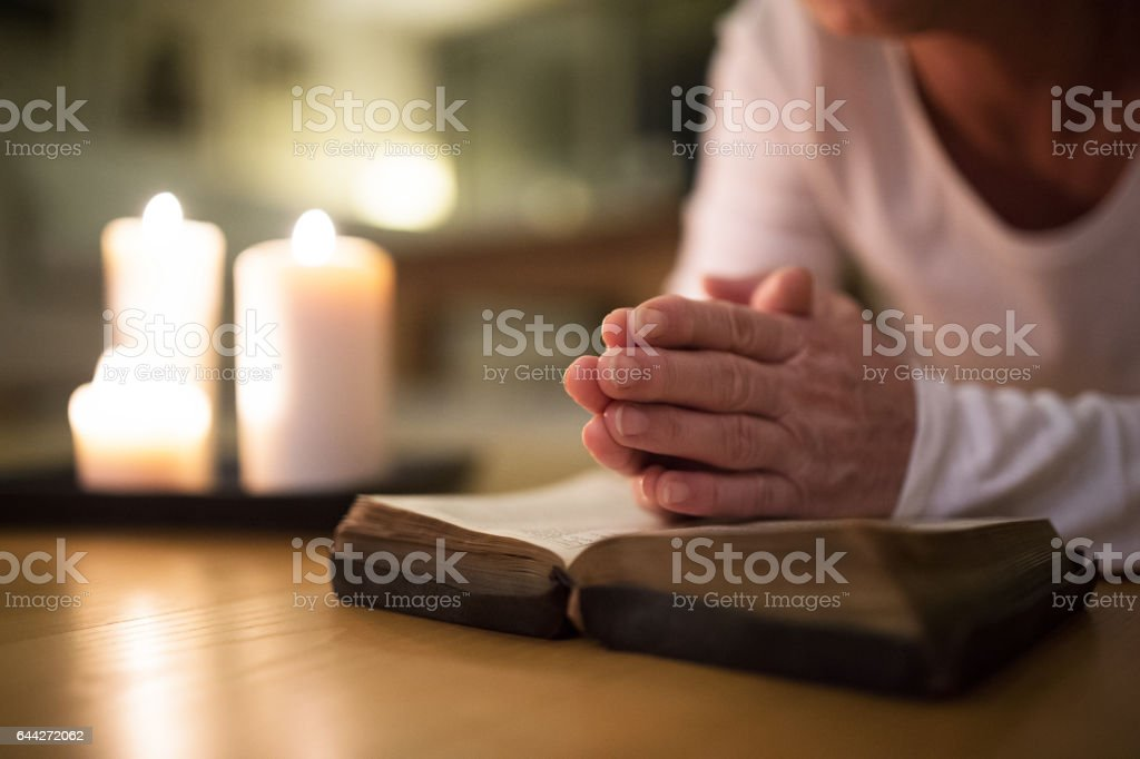 Unrecognizable senior woman praying, hands clasped together on her Bible. - foto de stock