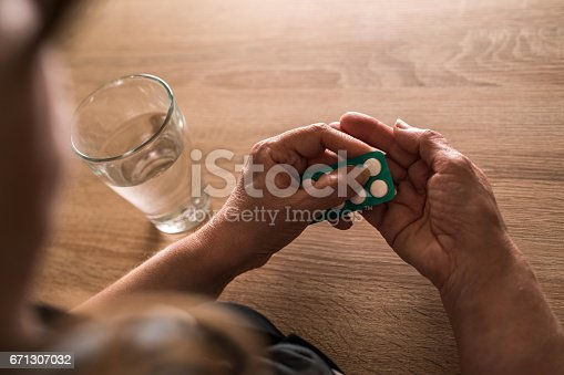 Close up of elderly woman taking a medicine out of blister pack. Close up of elderly woman taking a medicine out of blister pack.