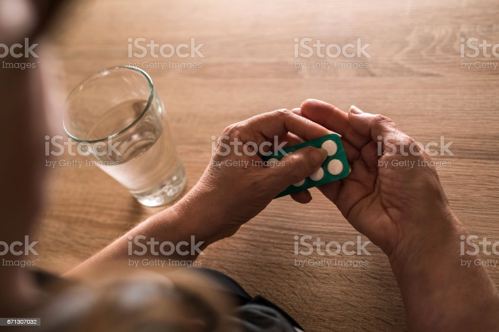 Unrecognizable senior woman taking a pill with a glass of water. stock photo