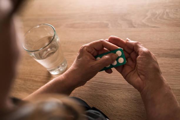 bir bardak su ile bir hap almaktan tanınmaz halde kadın kıdemli. - aspirin stok fotoğraflar ve resimler