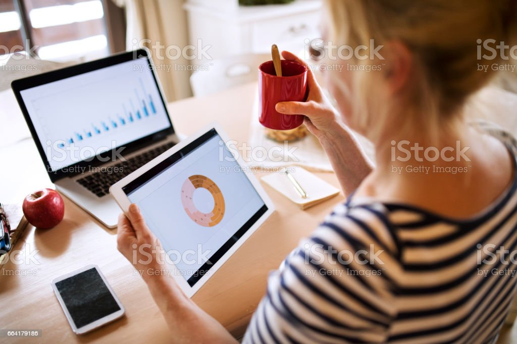 Unrecognizable senior woman with laptop and tablet at the kitchen table