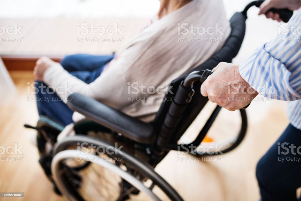 Unrecognizable senior women with wheelchair at home. stock photo