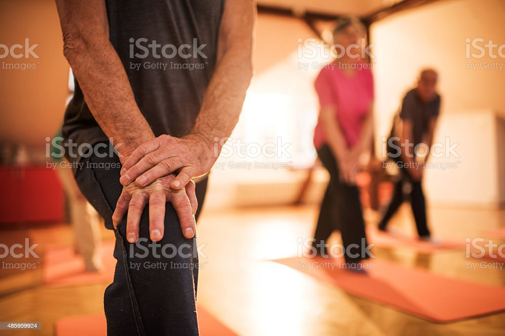 Unrecognizable seniors doing stretching exercises on a training. stock photo
