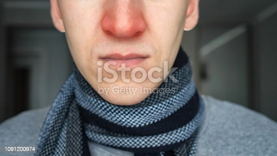 istock Unrecognizable sick guy in warm scarf with a red nose 1091200974