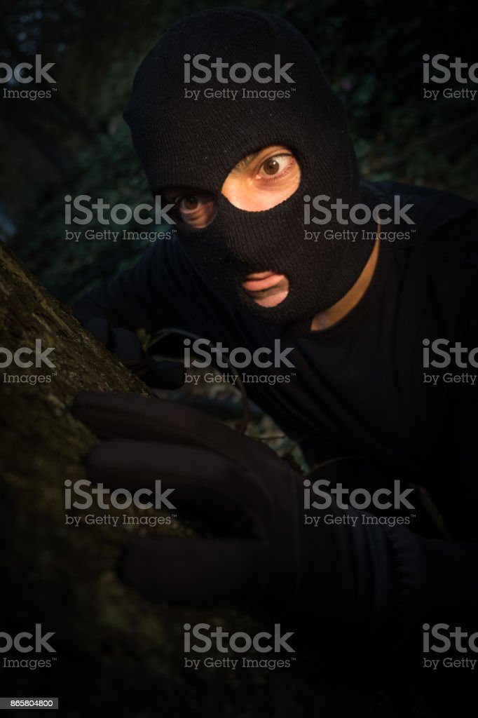 Unrecognizable sinister masked man skulking in the night - fotografia de stock