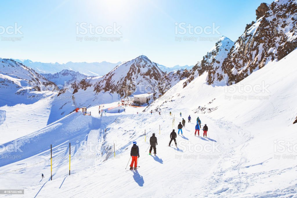 unrecognizable skiers on beautiful ski slope in Alps stock photo