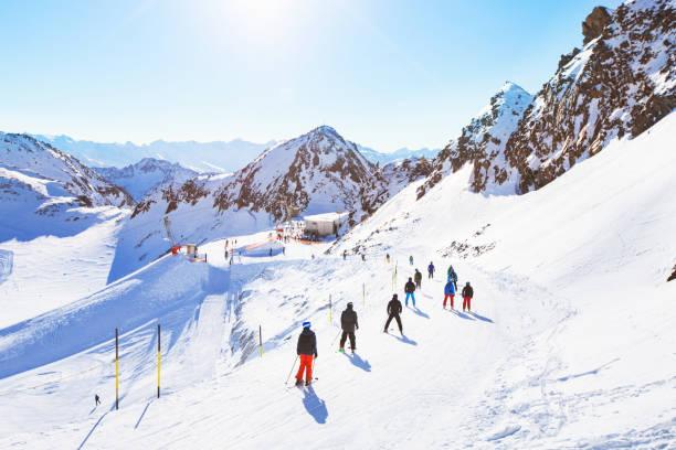 onherkenbaar skiërs op de helling van de mooie skigebieden in de alpen - skipiste stockfoto's en -beelden