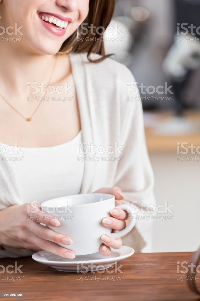 Unrecognizable smiling woman sits at table holding coffee mug stock photo