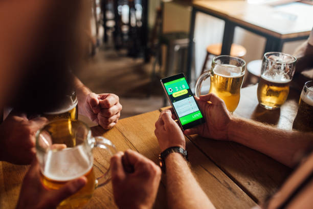 Unrecognizable soccer fans drinking beer at the pub and following betting results online stock photo