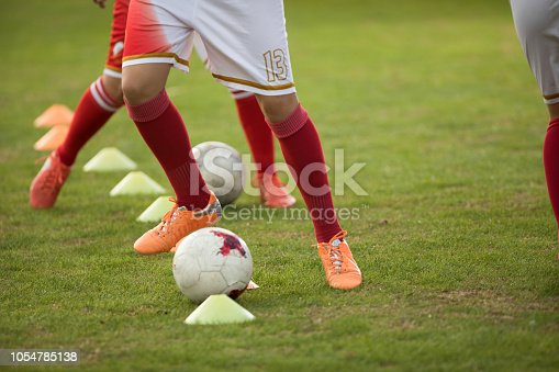 Team of unrecognizable soccer players practicing dribbling with ball on a playing field.