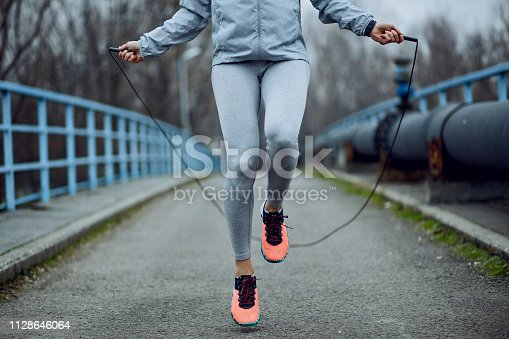 Unrecognizable female athlete exercising with jump rope while having a sports training outdoors.