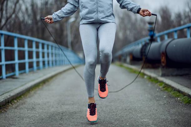 nicht erkennbare sportlerin seilspringen auf einer brücke. - springseil stock-fotos und bilder