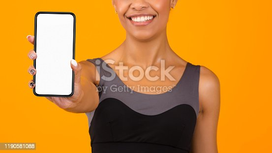 1132512759istockphoto Unrecognizable Sporty Afro Woman Showing Smartphone With Empty Screen, Panorama 1190581088