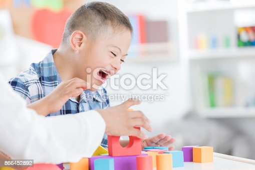 istock Unrecognizable teacher helps young boy with blocks 866452892
