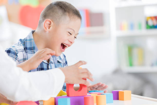 Unrecognizable teacher helps young boy with blocks stock photo