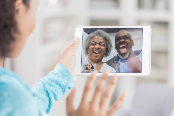 Unrecognizable teenage girl has videoconference with grandparents Unrecognizable teenage girl has videoconference with her grandparents. She is using a digital tablet. She is waving at her grandparents. long distance relationship stock pictures, royalty-free photos & images