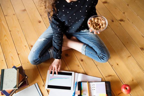Nicht erkennbare Teenager-Mädchen mit Tablet-PC auf dem Boden sitzend, Müsli zu essen, studieren – Foto