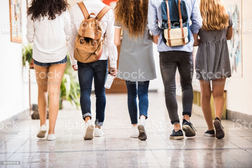 Unrecognizable teenage students in high school hall. stock photo