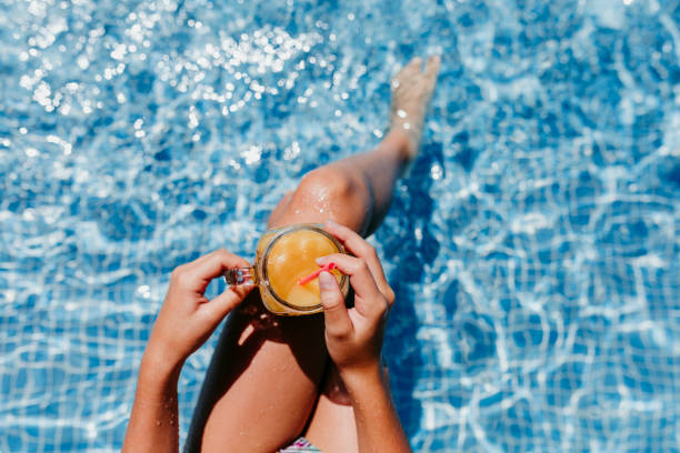 unrecognizable teenager girl at the pool drinking healthy orange juice and having fun outdoors. Summertime and lifestyle concept stock photo