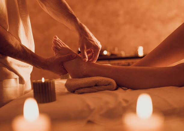 Unrecognizable therapist massaging customer's foot at health spa. Unrecognizable male therapist having relaxing foot massage with his customer at the spa. foot massage stock pictures, royalty-free photos & images