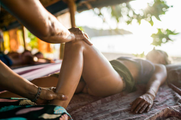 unrecognizable therapist massaging woman's leg at beauty spa. - thai massage stock photos and pictures