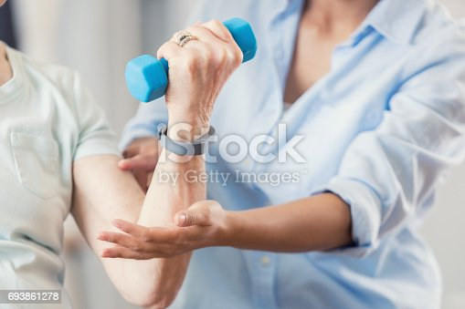 istock Unrecognizable uses blue hand weight during physical therapy session 693861278