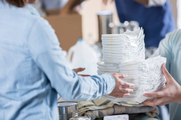 Unrecognizable volunteers organize diapers at local food bank stock photo