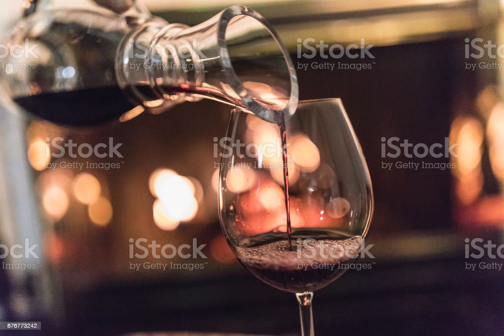 Unrecognizable woman, a decanter in her hands, pouring red wine in a glass. stock photo