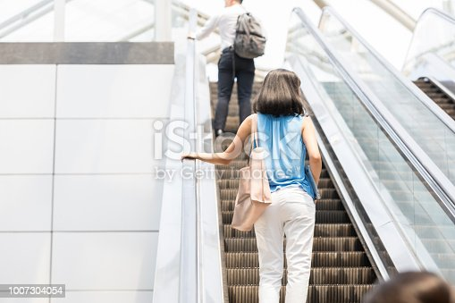 An unrecognizable woman holds the railing as she stands on an ascending escalator in the airport.