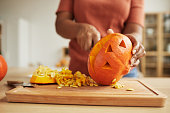 Unrecognizable African American woman standing at table carving Jack-O'-Lantern out of ripe orange pumpkin