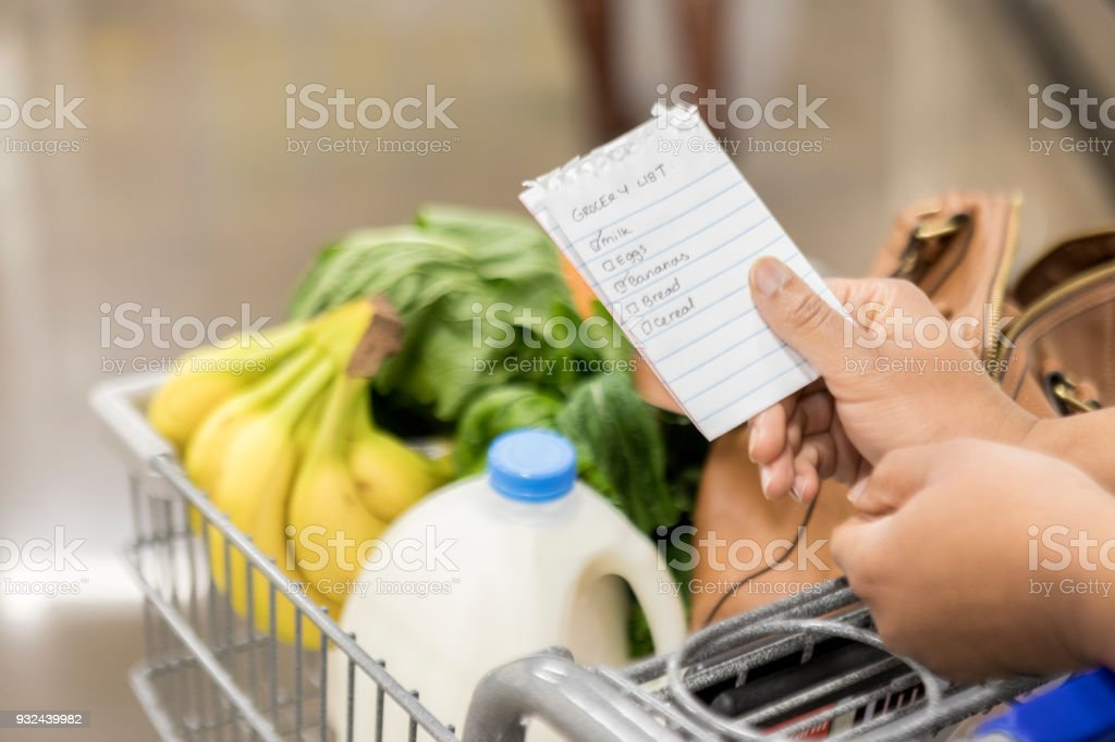 Unrecognizable woman checks items off grocery list stock photo