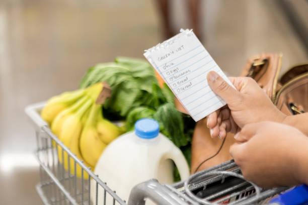 unrecognizable woman checks items off grocery list - icona supermercato foto e immagini stock
