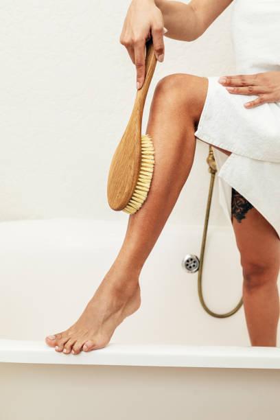 unerkennbare frau trocken putzen ihr bein im badezimmer - peeling bürste stock-fotos und bilder