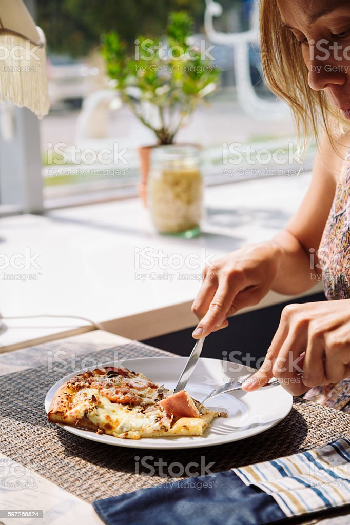 Unrecognizable woman eating pizza in cafe royalty-free stock photo