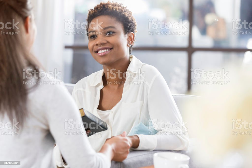 Unrecognizable woman gives her friend a Bible stock photo