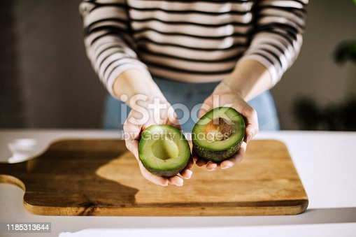 Unrecognizable woman holding in her hands opened avocado, close up