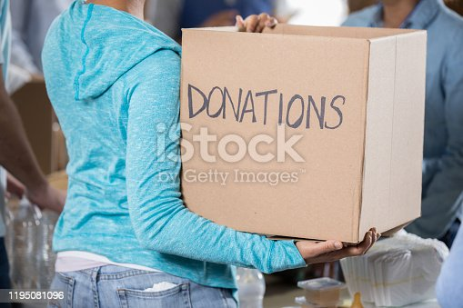 Unrecognizable woman holds a box filled with donated items during food drive.