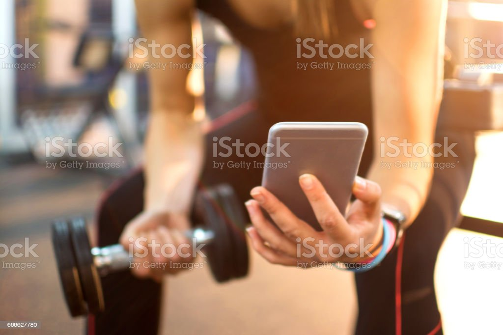 Unrecognizable woman holding mobile phone and weight in gym. Close up. - foto de stock