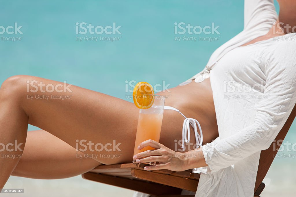 unrecognizable woman in a beach chair enjoying tropical cocktail stock photo