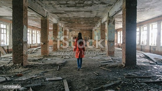 istock Unrecognizable woman in a red cloak inspects destroyed building after the disaster earthquake, flood, fire. 1070593800