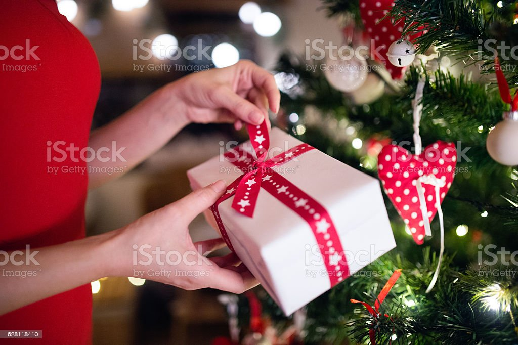 Unrecognizable woman in front of Christmas tree with present stock photo
