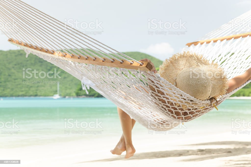 unrecognizable woman in hammock at Maho Bay Beach, St.John, USVI stock photo