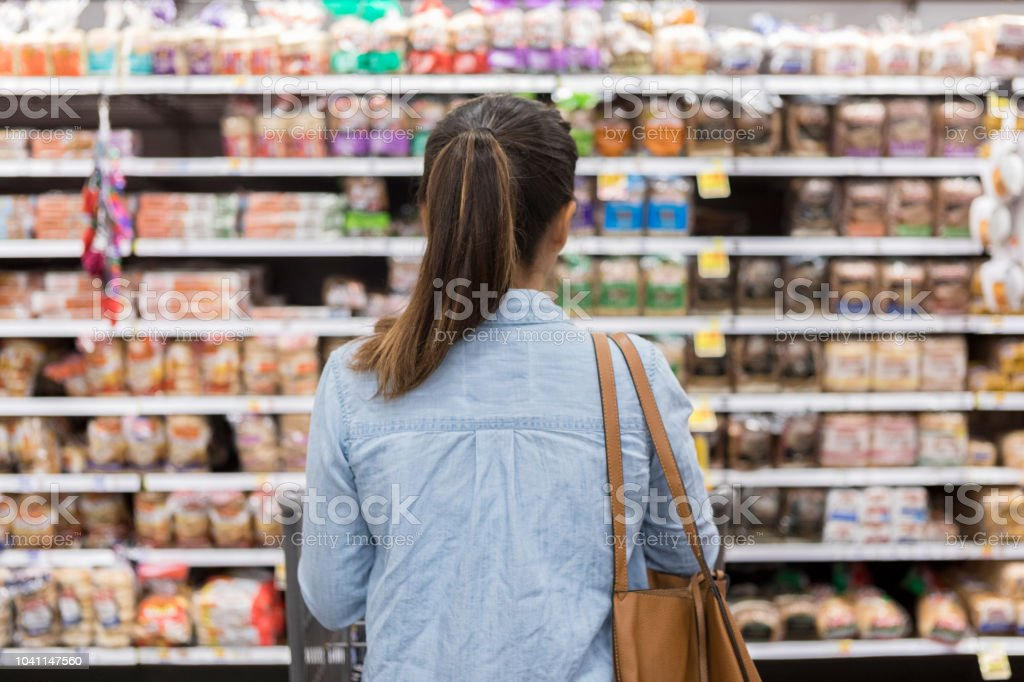 Unrecognizable woman marvels at grocery bread selection stock photo