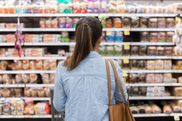 unrecognizable woman marvels at grocery bread selection - shopping stock photos and pictures
