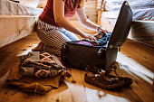 Unrecognizable woman packing luggage in log cabin, sitting on floor