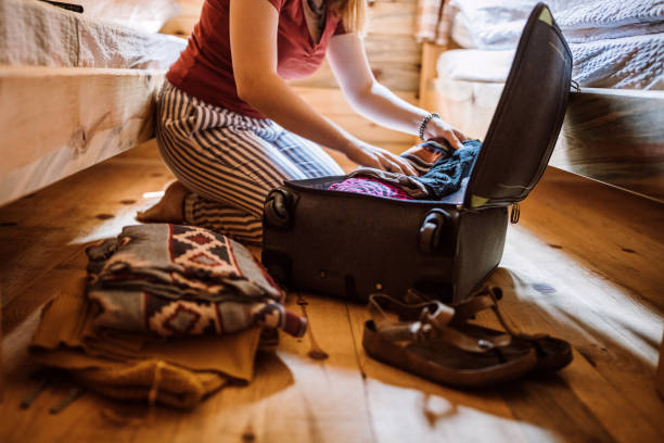 Unrecognizable woman packing luggage in log cabin stock photo